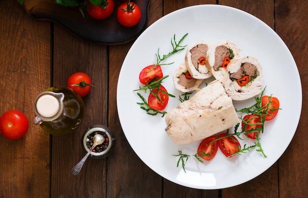Dieta al horno rollos de pollo rellenos de hígado, chile y hierbas con una ensalada de tomates y rúcula. menú dietético nutrición apropiada. vista superior