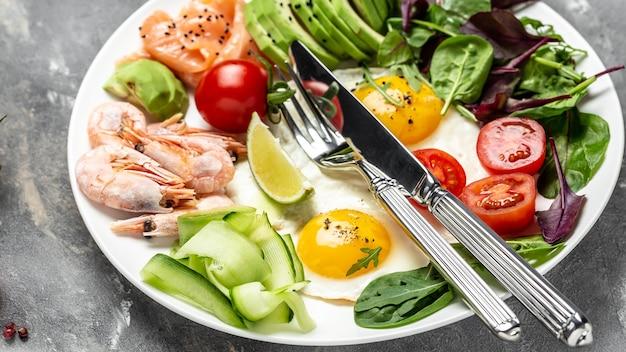 Dieta cetogénica, paleo baja en carbohidratos desayuno de salmón, camarones hervidos, camarones, huevos fritos, ensalada fresca, tomates, pepinos y aguacate. vista superior. fondo de receta de comida. de cerca.