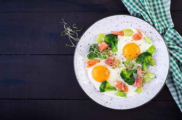 Dieta cetogénica / paleo. huevos fritos, salmón, brócoli y microverdes. desayuno keto. desayuno tardío. vista superior, arriba