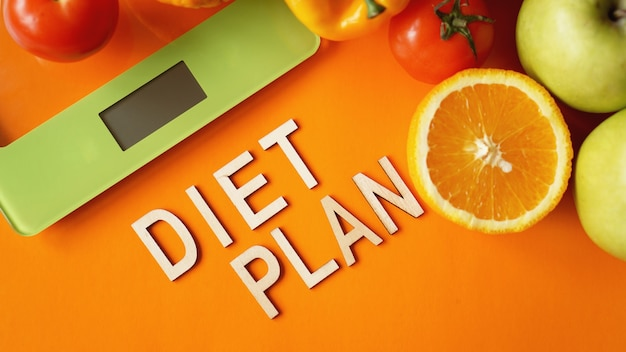 Dieta de concepto. comida sana, báscula de cocina. plan de dieta de letras de verduras y frutas
