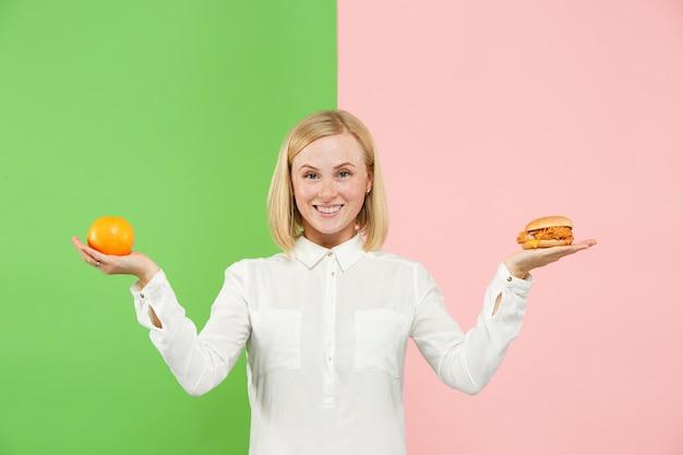 Dieta. concepto de dieta. comida sana. hermosa joven eligiendo entre frutas y comida rápida poco saludable