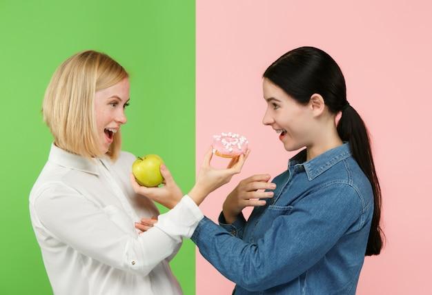 Dieta. concepto de dieta. comida sana. hermosas mujeres jóvenes eligiendo entre frutas y pastel poco saludable