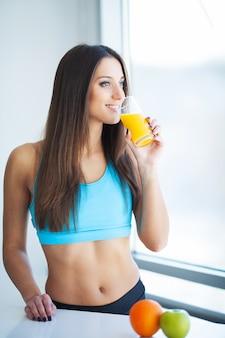 Dieta y haelth. colocar sonriente mujer joven con jugo saludable en la cocina moderna