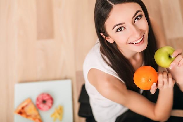 Dieta. una joven observa su figura y come fruta fresca. el concepto de alimentación saludable.