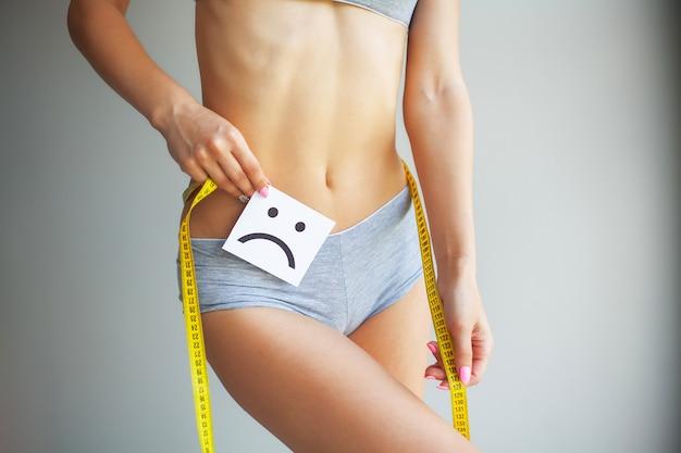 Dieta manos midiendo la cintura con una cinta. mujer delgada y sana en su casa