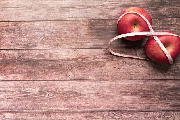 Dieta manzana roja se unen con cinta métrica en el fondo de madera
