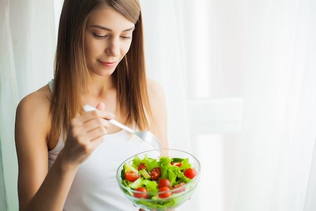 Dieta. mujer joven comiendo ensalada y sosteniendo una ensalada mixta