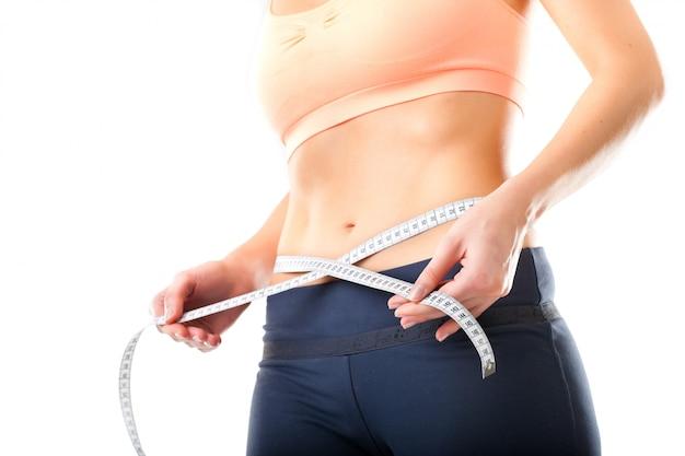 Dieta: una mujer joven mide su cintura