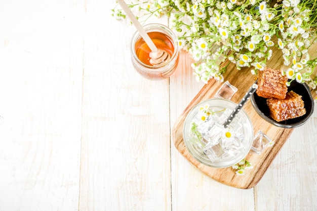 Dieta orgánica detox bebida de verano, bebida de agua infundida con manzanilla y miel, en mesa de madera blanca, con flores de manzanilla y miel en un frasco. copia espacio