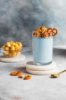 Dieta panna cotta con yogur griego, leche de coco, espirulina azul decorada con palomitas de maíz y pretzel en el vaso. concepto probiótico desayuno saludable. de cerca