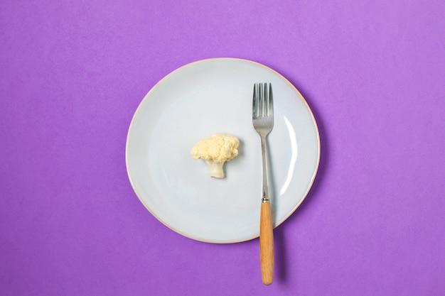 Dieta, pérdida de peso mínima, coliflor saludable en placa, vista superior, copyspace, púrpura.