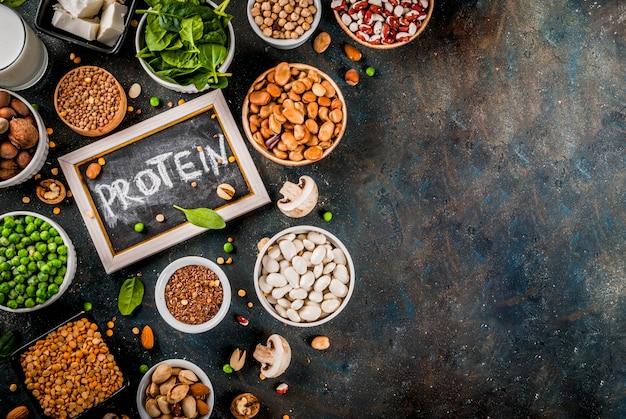 Dieta saludable comida vegana, fuentes de proteínas vegetales: tofu, leche vegana, frijoles, lentejas, nueces, leche de soja, espinacas y semillas. vista superior de la mesa blanca.