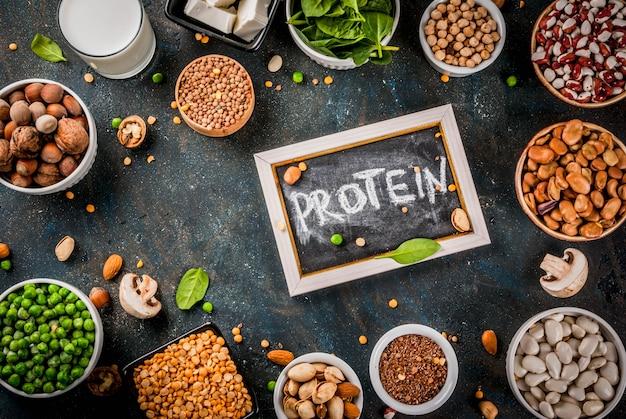Dieta saludable comida vegana fuentes de proteínas vegetarianas tofu vegano leche frijoles lentejas nueces leche de soja espinacas y semillas en mesa blanca