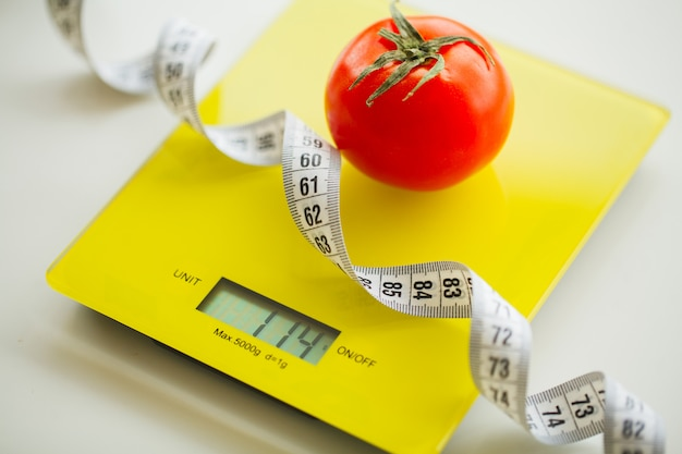 Dieta, tomate con cinta métrica en báscula