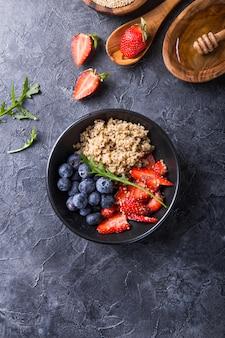 Dieta vegana saludable ensalada de quinua con semillas de arándano, fresa, miel y chía.