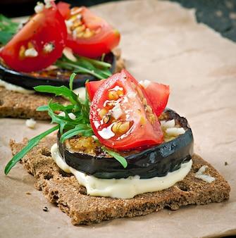 Dieta vegetariana sandwiches de pan crujiente con queso crema de ajo, berenjenas asadas, rúcula y tomates cherry sobre fondo de madera vieja