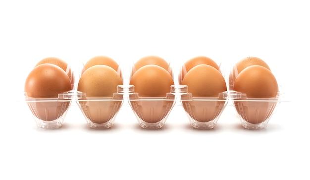 A diez huevos al costado del envase plástico abierto.