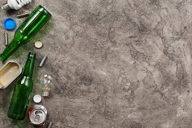 Diferente basura surtida para reciclar sobre fondo gris.