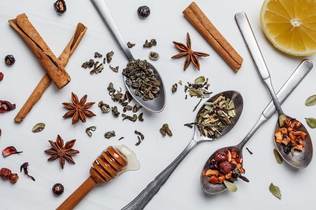 Diferente té de hierbas con miel, limón y especias sobre fondo blanco.
