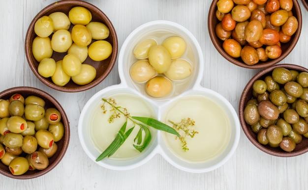Diferentes aceitunas con hojas y aceite de oliva en una arcilla y cuencos blancos sobre madera blanca, primer plano.