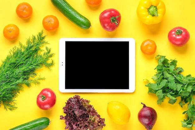 Diferentes alimentos saludables: pimiento, tomates, plátanos, pepino verde, cebolla, limón, tableta con pantalla negra