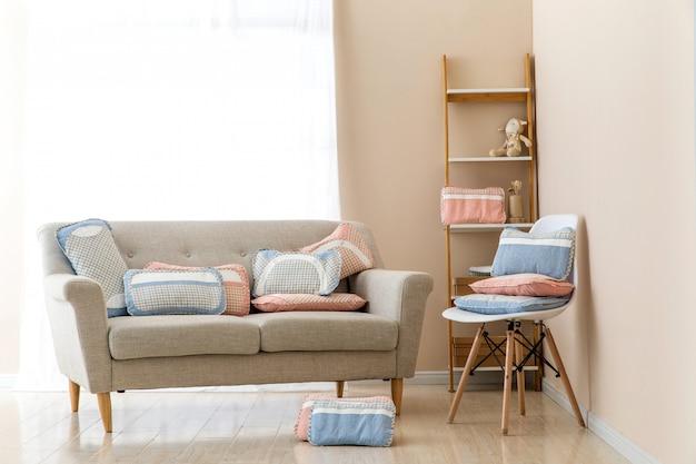 Diferentes almohadas en silla en habitación