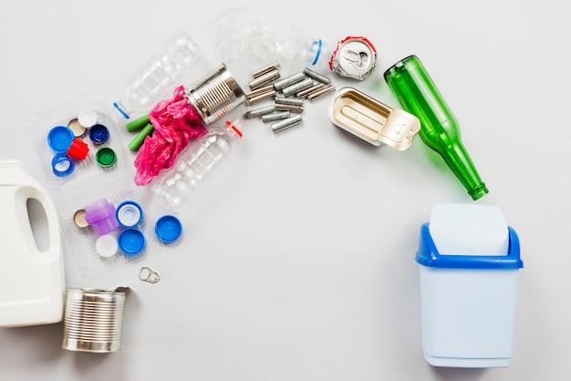 Diferentes basureros reciclables vertidos en bote de basura.
