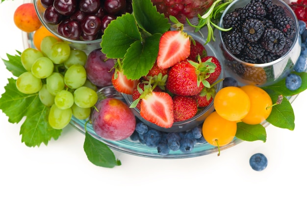 Diferentes bayas de verano grosella roja, grosella, frambuesa en bandejas de vidrio