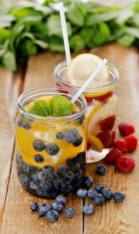 Diferentes bebidas frías con pajitas en una mesa de madera