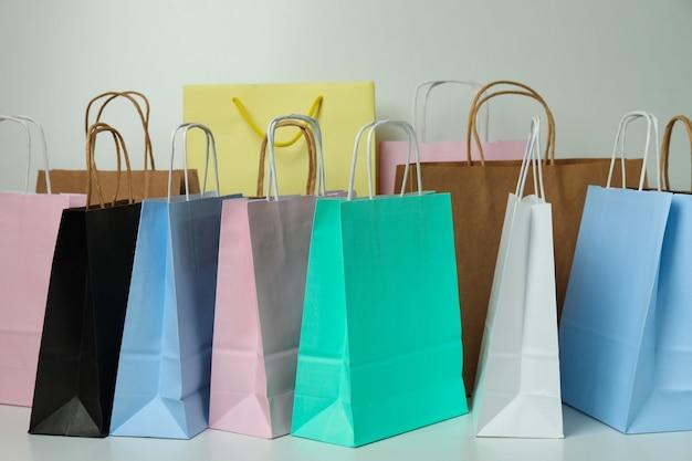 Diferentes bolsas de papel de colores sobre fondo blanco.