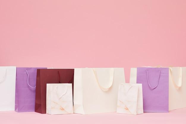Diferentes bolsas de papel de compras aisladas sobre fondo rosa