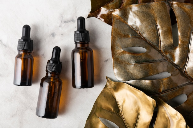 Diferentes botellas para aceites para el cuidado de la piel sobre fondo de mármol