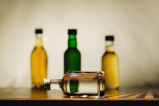 Diferentes botellas de alcohol están sobre la mesa en una luz.
