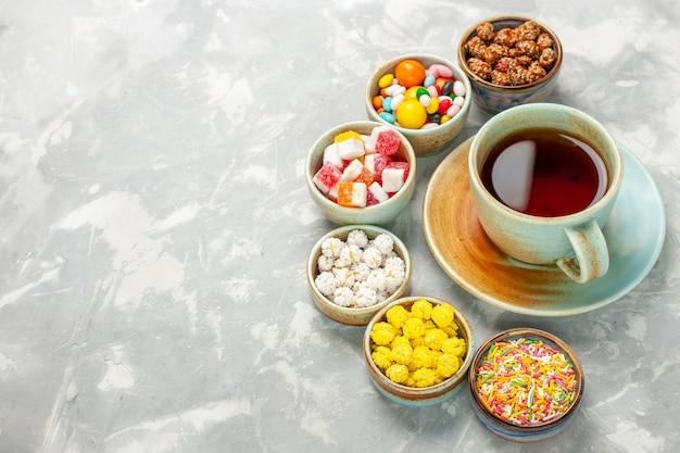 Diferentes caramelos dulces con malvaviscos y taza de té en el escritorio blanco