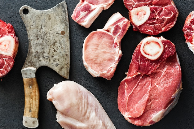 Diferentes carnes carne de cerdo pollo filete de res cuchillo de carnicero vista superior negra