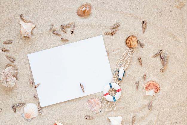 Diferentes conchas de mar con papel en blanco sobre arena.