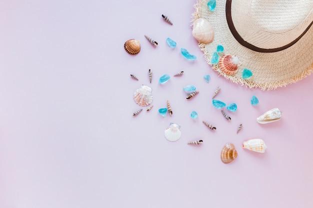 Diferentes conchas de mar con sombrero de paja.