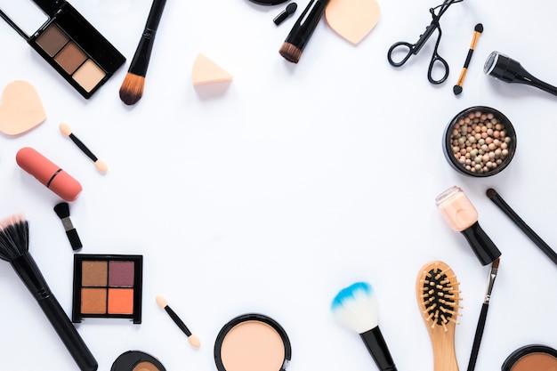 Diferentes cosméticos con herramientas en mesa.