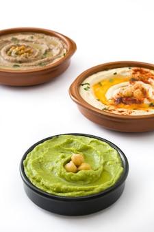 Diferentes cuencos de hummus hummus de garbanzos, hummus de aguacate y hummus de lentejas aislado en blanco