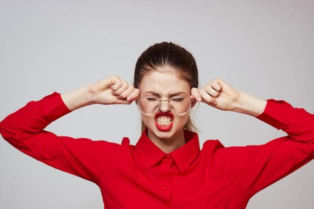 Diferentes emociones mujer joven en ropa roja sobre un fondo claro