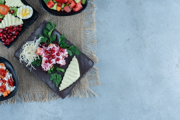 Diferentes ensaladas en bandejas sobre mármol.