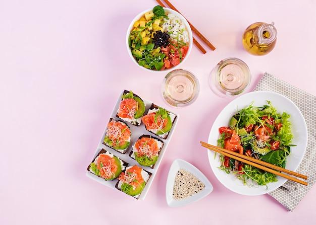 Diferentes ensaladas saludables y sándwiches de salmón.