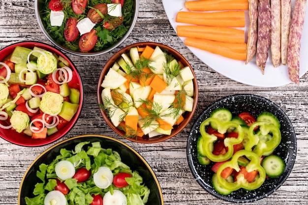 Diferentes ensaladas de verduras en diferentes tazones sobre superficie de madera blanca frijoles pimiento zanahoria cebolla lechuga vista superior