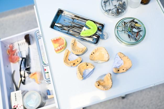 Diferentes equipos dentales profesionales, instrumentos y herramientas en una clínica de oficina de estomatología de dentistas sobre un fondo blanco. molde de silicona de la mandíbula.
