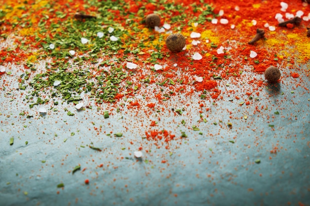 Diferentes especias esparcidas sobre la mesa, pimentón rojo en polvo, cúrcuma, sal, clavo, pimienta. enfoque selectivo