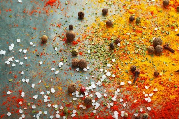 Diferentes especias esparcidas sobre la mesa, pimentón rojo en polvo, cúrcuma, sal, clavo, pimienta.