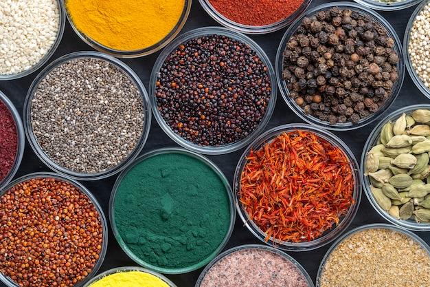 Diferentes especias y hierbas en el fondo, primer plano, vista superior. surtido de especias coloridas, semillas y hierbas para cocinar alimentos