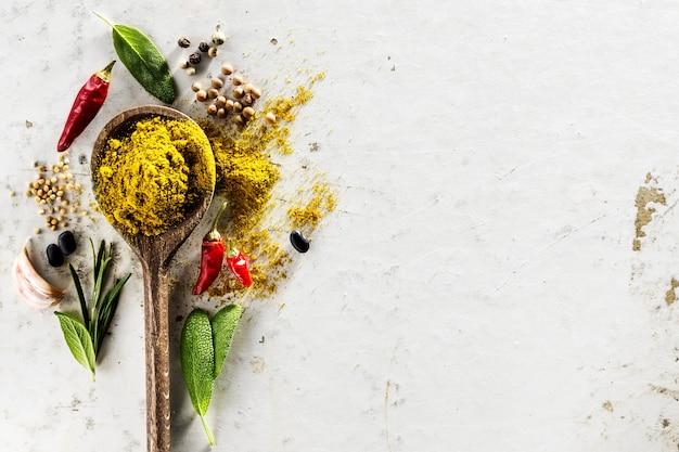 Diferentes especias ingredientes de alimentos cuchara de madera sobre fondo blancotable