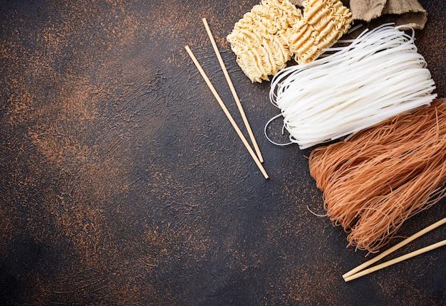 Diferentes fideos de arroz asiático sobre fondo oxidado