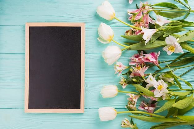 Diferentes flores brillantes con pizarra en la mesa